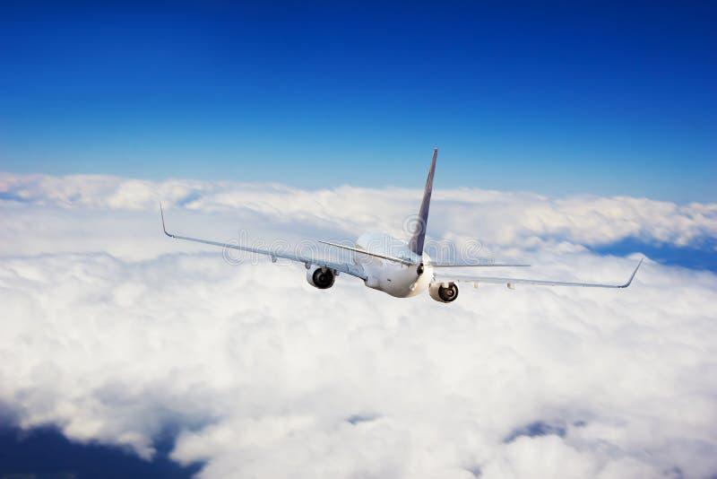 Коммерчески летание реактивного самолета над облаками стоковые фото
