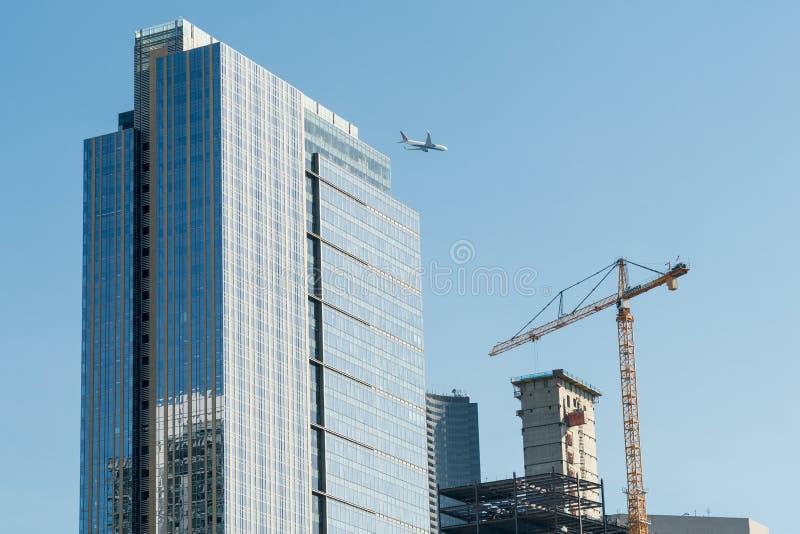 Коммерчески самолет перелетает между небоскребом и краном в небе Сиэт стоковое фото