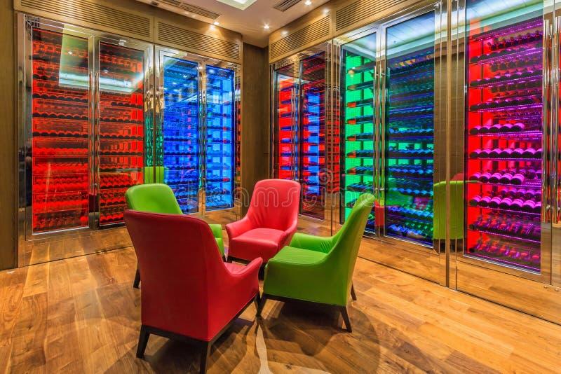 Комната вина гостиницы Solis Сочи выполнена в современном стиле с красочным освещением Много бутылок вина лежат на полках в клетк стоковые изображения