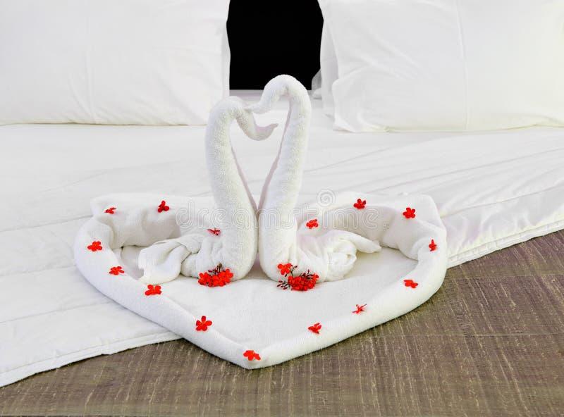 Комната в гостинице с лебедями от полотенца на новобрачных кладет в постель стоковые фотографии rf