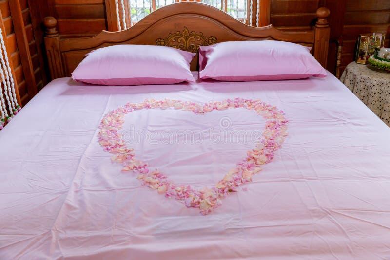 Комната кровати в костюмах роскошного медового месяца сладких Кровать луны меда Медовый месяц, кровать свадьбы покрыл с лепесткам стоковая фотография