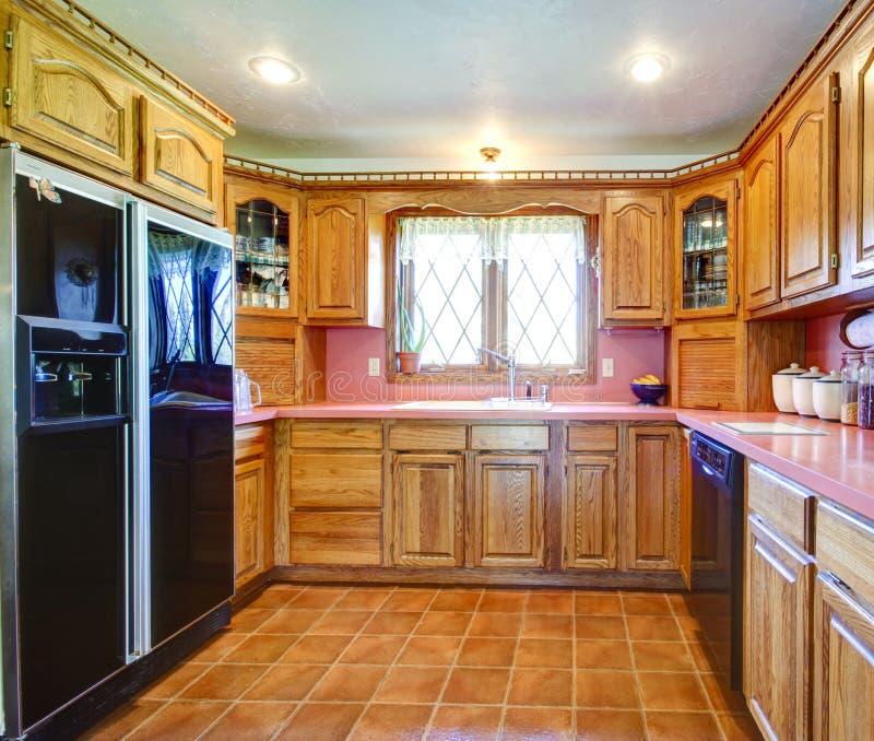Комната кухни сельского дома с деревянными шкафами и розовым backsplash стоковая фотография