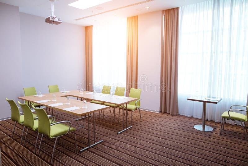 Комната офиса с зелеными стульями, большими и малыми таблицами и видео- репроектором стоковые фото