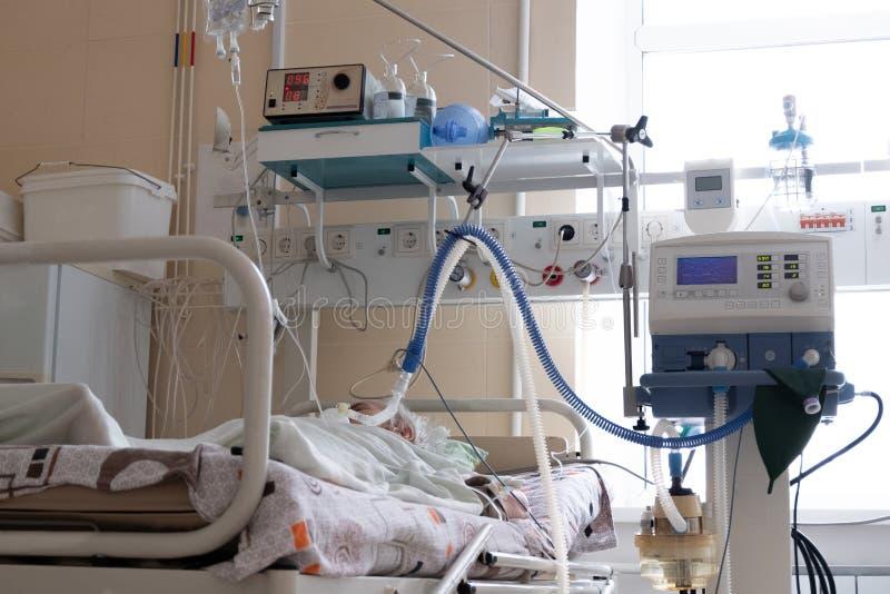 Комната реаниматологии в больнице Лож серьезно больные старика на его кровати Медицинское оборудование стоковые изображения rf