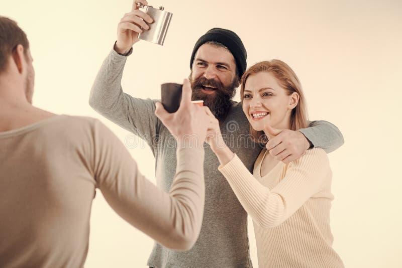 Компания жизнерадостных друзей тратит отдых с пить Парни держат чашку, склянку с спиртом, говорят Люди, женщина на усмехаться стоковые фото