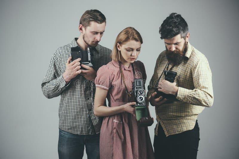 Компания занятых фотографов со старыми камерами, киносъемка, работая Люди в checkered одеждах, ретро стиле r стоковые фото