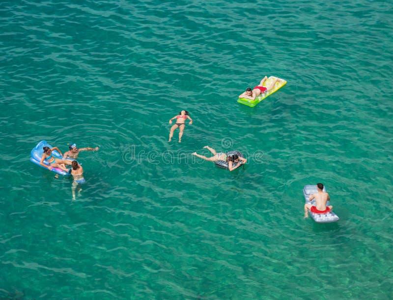 Компания молодые люди на тюфяках воздуха в море стоковая фотография rf