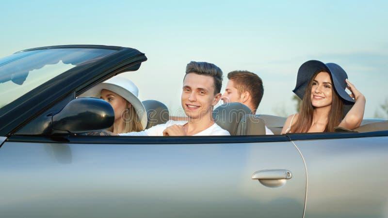 Компания сидя в cabriolet, путешествуя на автомобиле стоковые фото