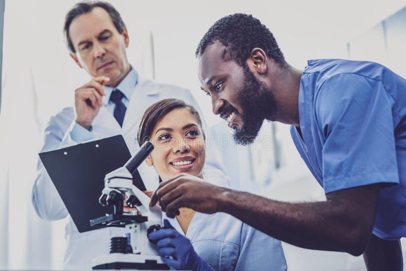 Компания 3 bioengineers имея встречу штата стоковые изображения