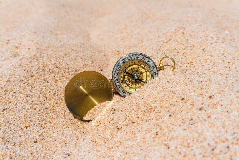 Компас в песке золота на пляже взрослые молодые стоковые изображения rf