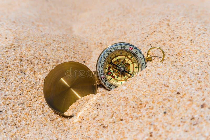 Компас в песке золота на пляже взрослые молодые стоковое изображение rf