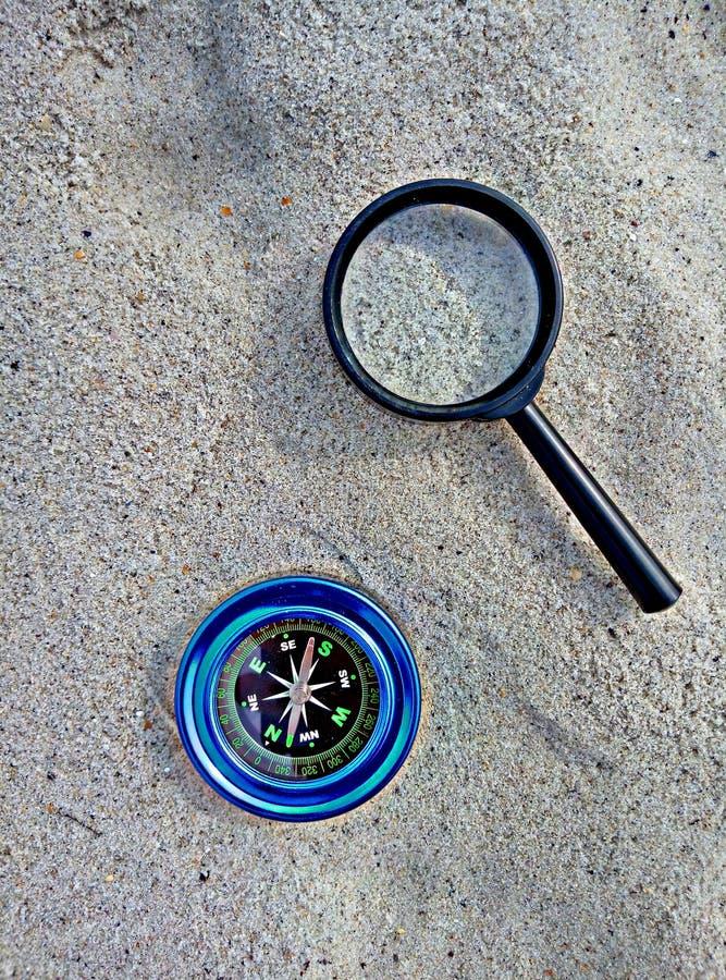 Компас и увеличитель на песке стоковые изображения