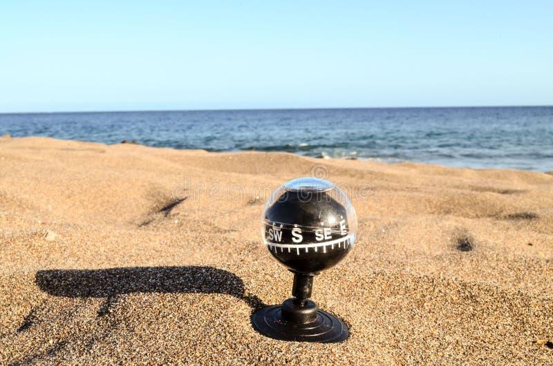 Компас на пляже песка стоковая фотография