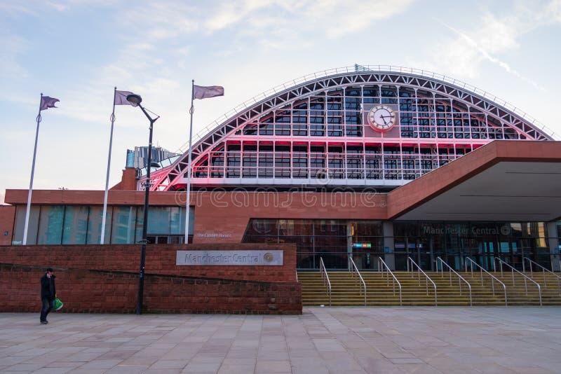 Комплекс конвенции Манчестера центральный в Великобритании по мере того как человек держа мобильный телефон идет мимо Бывшая желе стоковые изображения rf