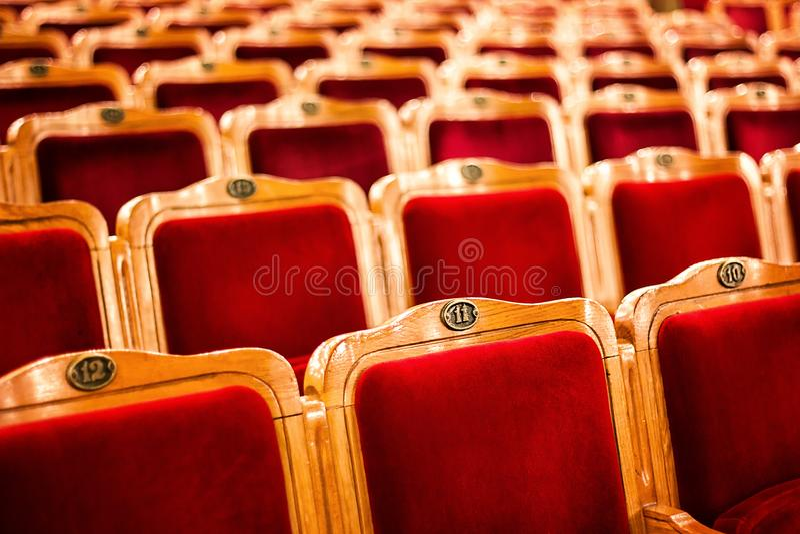 Комплекты на пустом театре, принятом с селективным фокусом и малой глубиной поля Пустые винтажные красные места с номерами, cha t стоковые изображения rf