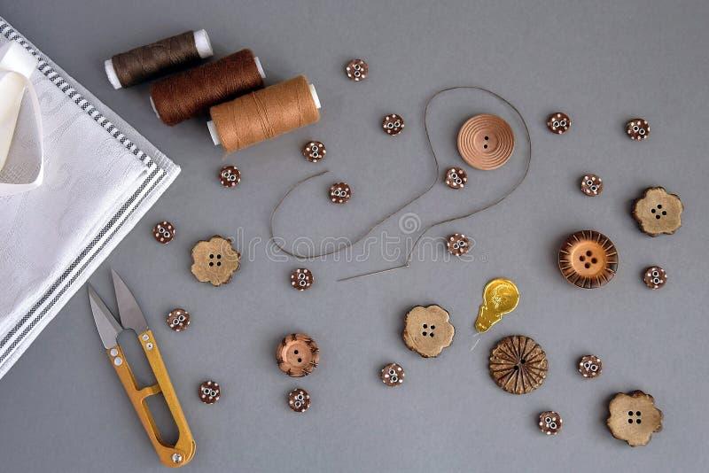 Комплект аксессуаров для шитья и шитья: кнопки, ножницы, иголка с ниткой, коричневые нити, ткань и лента стоковое фото rf