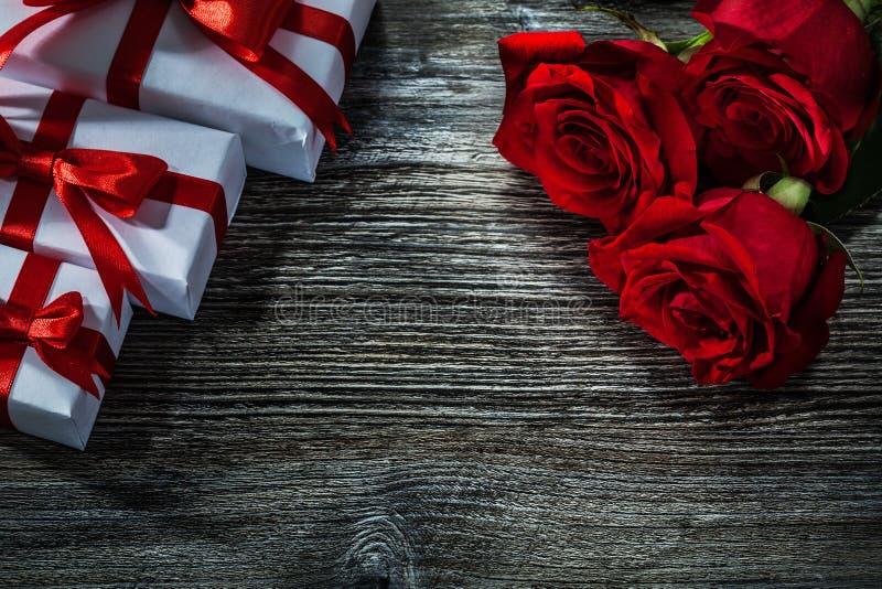 Комплект белого присутствующего пука коробок красных роз на деревянной доске стоковые фотографии rf