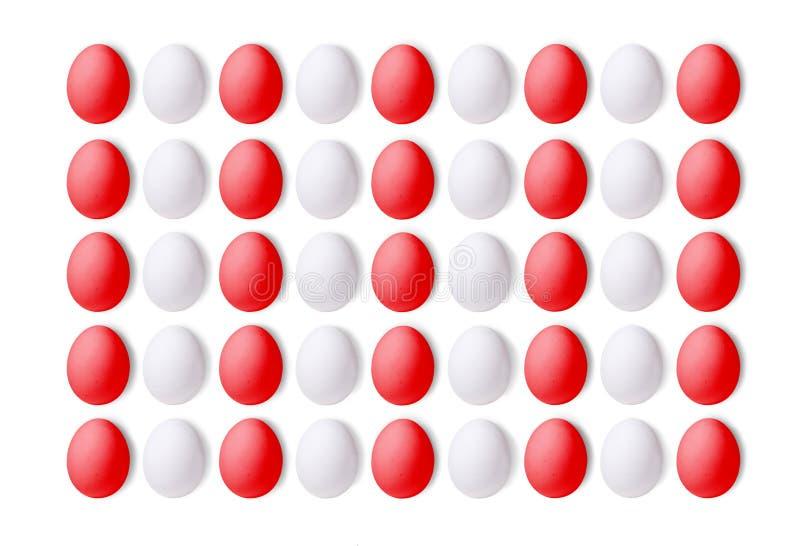 Комплект белых и красных яичек на белой предпосылке, положенный в вертикальные линии Конец-вверх стоковая фотография