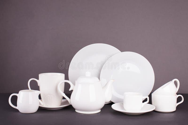 Комплект белых утварей для обеда и чаепития на серой предпосылке стоковое фото