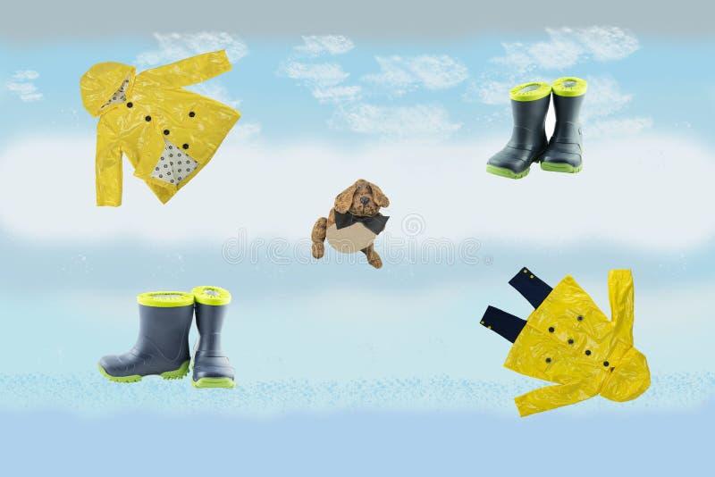 Комплект ботинок плаща и ribber на абстрактном голубом ярком backround, смешной игрушке стоковое фото