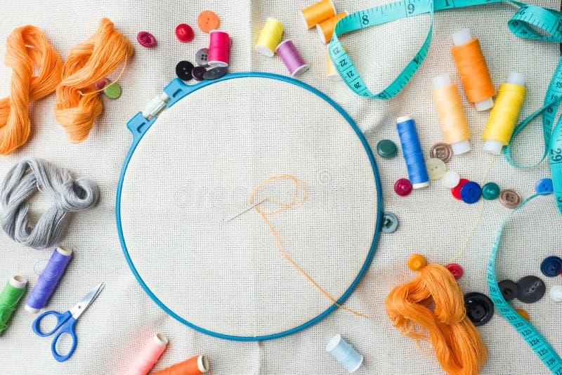 Комплект вышивки Белая ткань белья, обруч вышивки, красочные потоки и needls скопируйте космос стоковая фотография