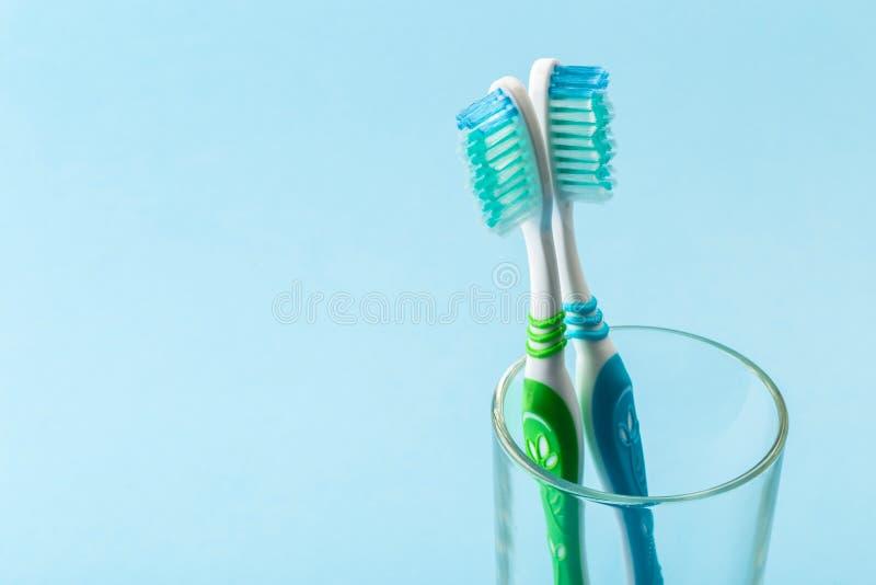 Комплект зубных щеток в стекле на голубой предпосылке стоковые фото