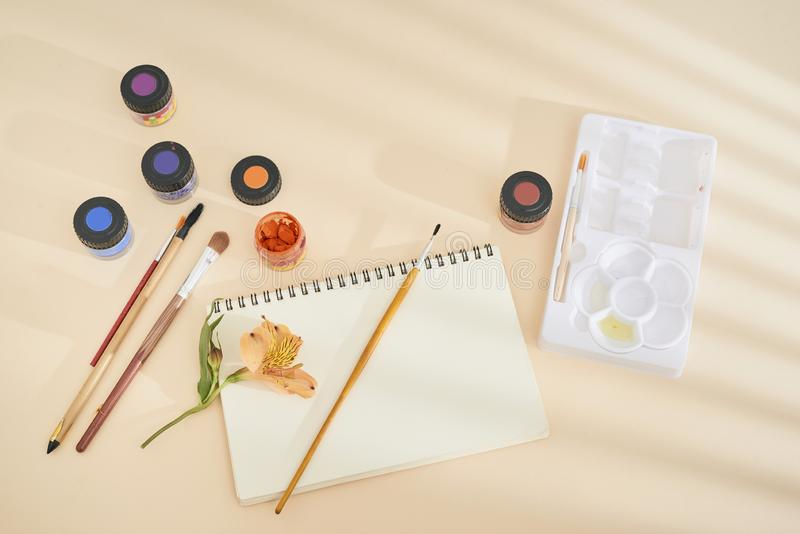 Комплект краски акварели, щеток искусства и бумаги на столе стоковые фотографии rf