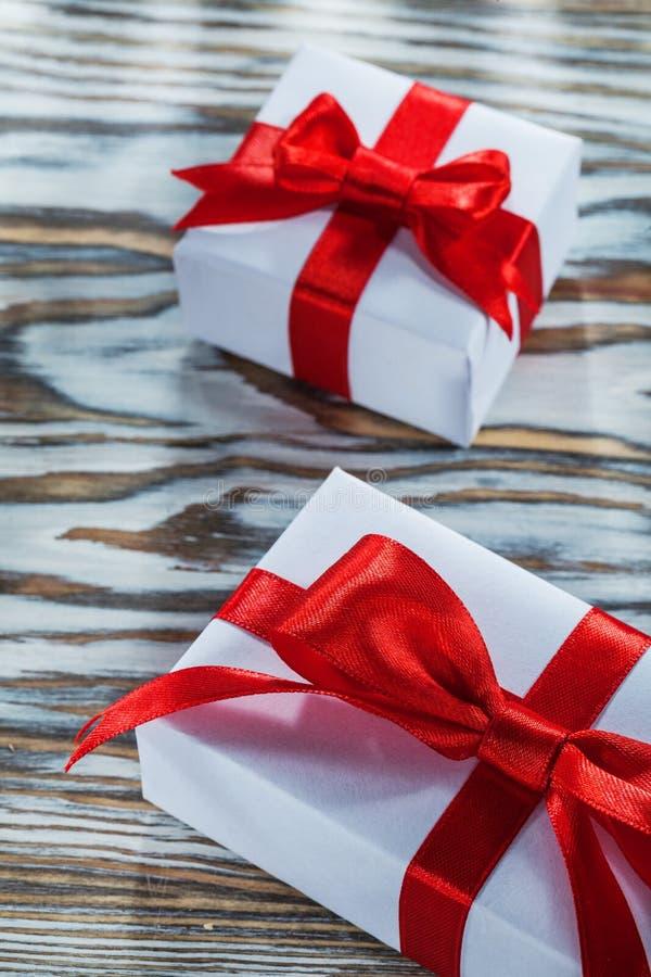 Комплект красного цвета обернул присутствующие коробки на деревянной поверхности стоковые изображения