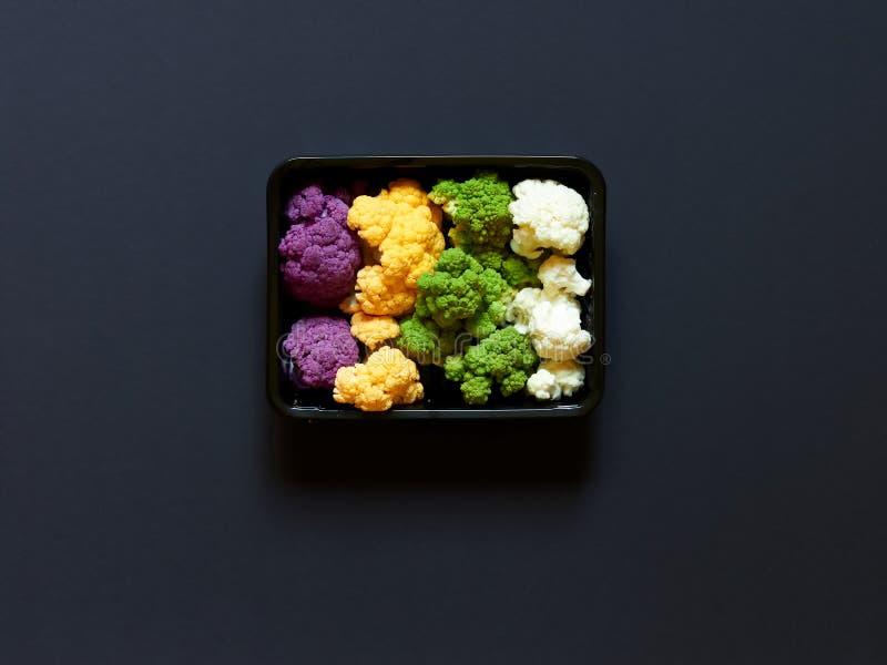 Комплект красочной цветной капусты фиолетовый, желтый, зеленый и белизны положил в коробку - в пластичном получателе над черной п стоковая фотография