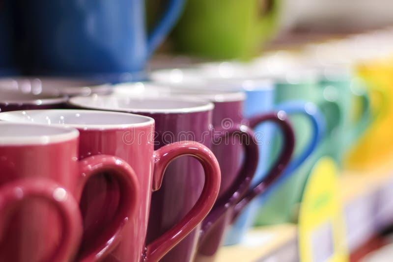 комплект красочных чашек кружки на старом деревянном столе, запачканной предпосылке стоковая фотография