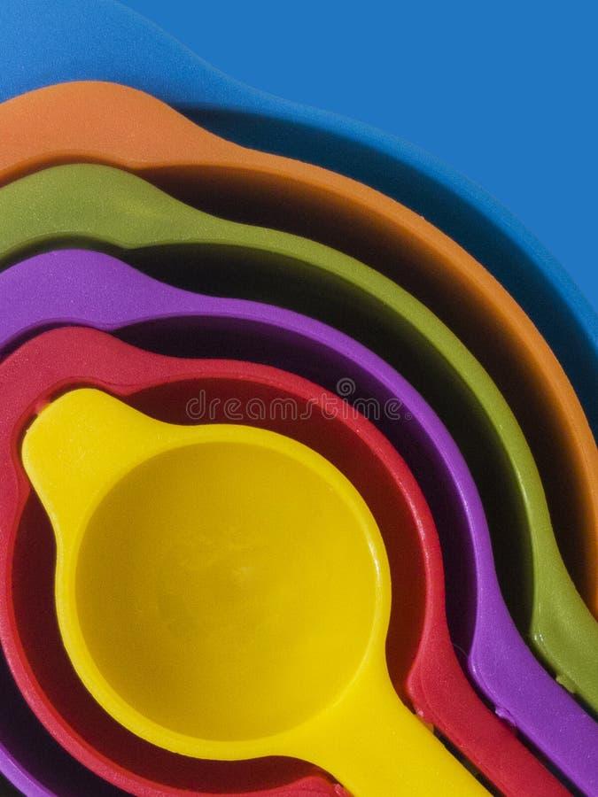 Комплект мерной ложки из красочного пластика на синем фоне, кухонное оборудование стоковая фотография rf