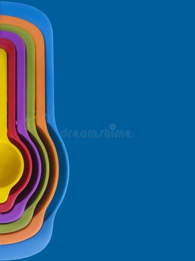Комплект мерной ложки из красочного пластика на синем фоне, кухонное оборудование стоковые фотографии rf