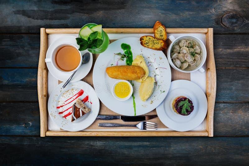 Комплект обеда Вареники, куриная котлета с картофельным пюре и русский салат сельдей, служили со столовым прибором стоковые фото