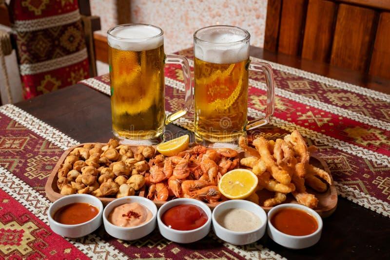 Комплект пива 2 пив и закуски на деревянной плите с 5 соусами На деревянном столе со скатертью с национальными картинами стоковое изображение rf