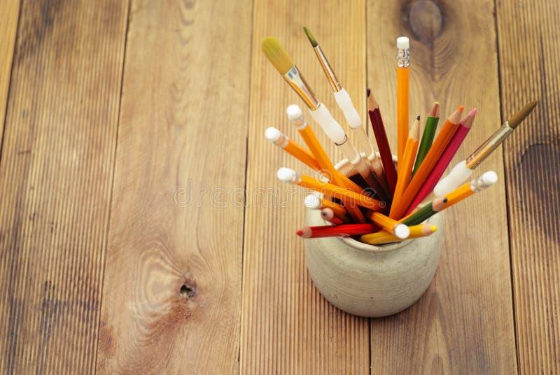 Комплект покрашенных карандашей в керамическом стекле на предпосылке деревянного стола задняя школа принципиальной схемы к Предпо стоковое изображение rf