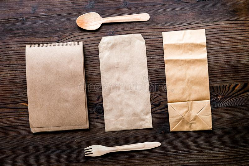 Комплект поставки с бумажными мешками и flatware на деревянной предпосылке t стоковое изображение