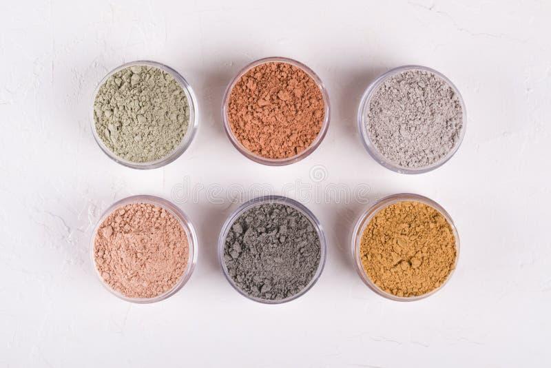 Комплект различных косметических порошков грязи глины на белизне стоковые фотографии rf