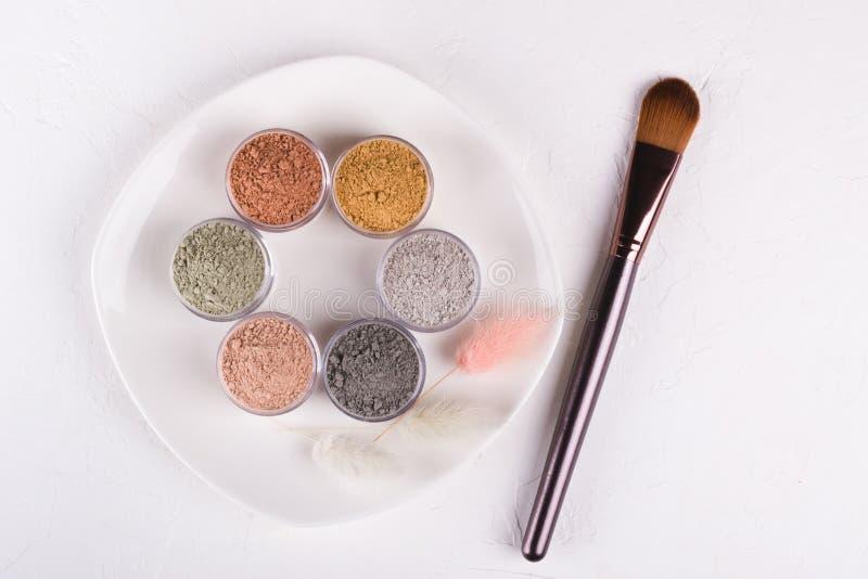 Комплект различных косметических порошков грязи глины на белизне стоковые изображения rf