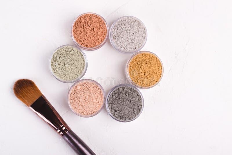 Комплект различных косметических порошков грязи глины на белизне стоковое изображение