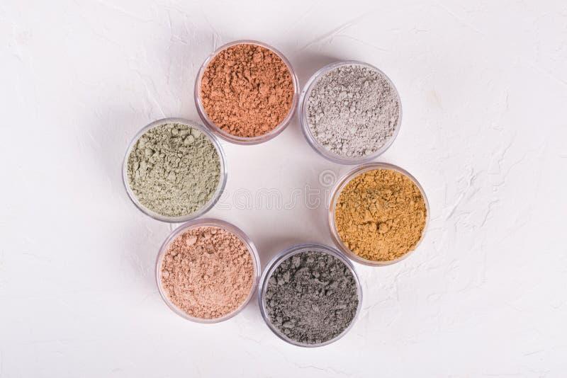 Комплект различных косметических порошков грязи глины на белизне стоковое фото