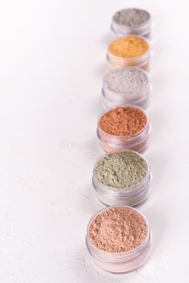 Комплект различных косметических порошков грязи глины на белизне стоковые изображения