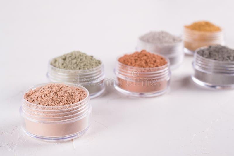Комплект различных косметических порошков грязи глины на белизне стоковое изображение rf