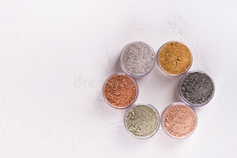 Комплект различных косметических порошков грязи глины на белизне стоковая фотография rf