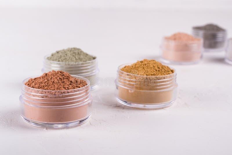 Комплект различных косметических порошков грязи глины на белизне стоковая фотография