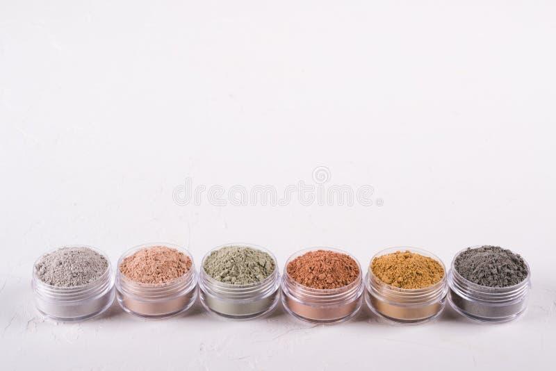 Комплект различных косметических порошков грязи глины на белизне стоковые фото