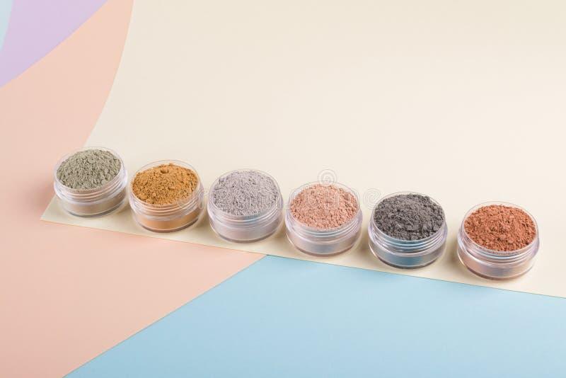 Комплект различных косметических порошков грязи глины на пестротканой предпосылке стоковые изображения rf