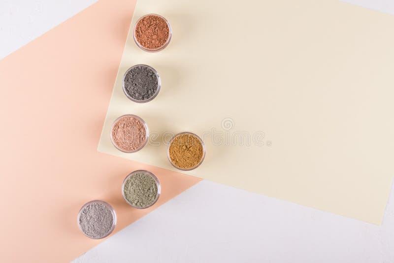 Комплект различных косметических порошков грязи глины на пестротканой предпосылке стоковое изображение