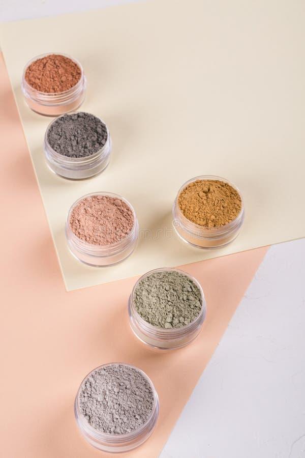 Комплект различных косметических порошков грязи глины на пестротканой предпосылке стоковое фото rf