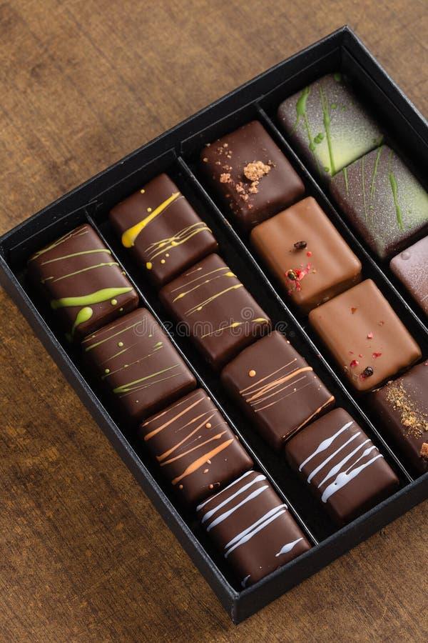 Комплект роскошных handmade bonbons в подарочной коробке на деревянном backgroun стоковая фотография