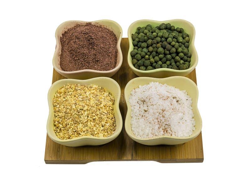 Комплект соли чеснока кориандра специй земных и пимента в керамических зеленых шарах на деревянной предпосылке планки стоковые фото